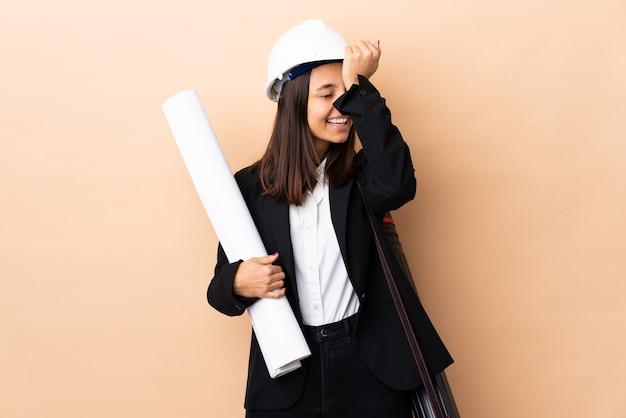 격리 된 벽 위에 청사진을 들고 젊은 건축가 여자는 뭔가를 실현하고 솔루션을 계획하고 있습니다