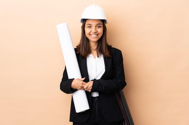 팔을 유지하는 격리 된 벽 위에 청사진을 들고 젊은 건축가 여자가 정면 위치에서 넘어