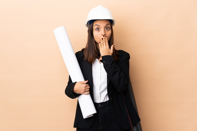 Young architect woman holding blueprints over wall covering mouth with hand