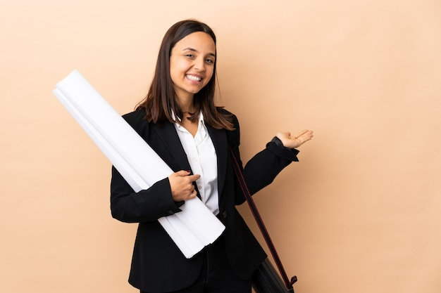 Young architect woman holding blueprints over wall extending hands to the side for inviting to come