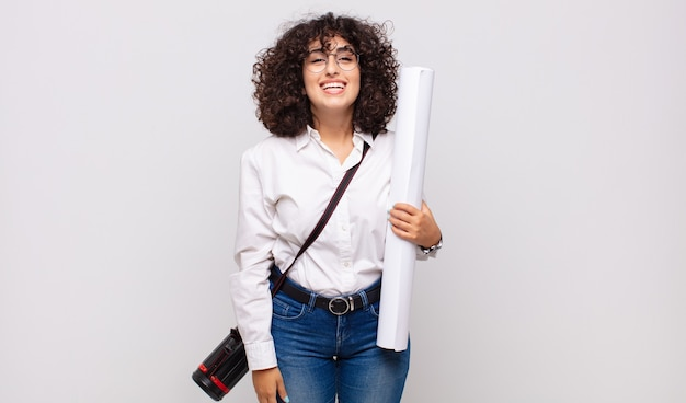 Молодая женщина-архитектор выглядит счастливой и приятно удивленной, взволнованной с очарованным и шокированным выражением лица