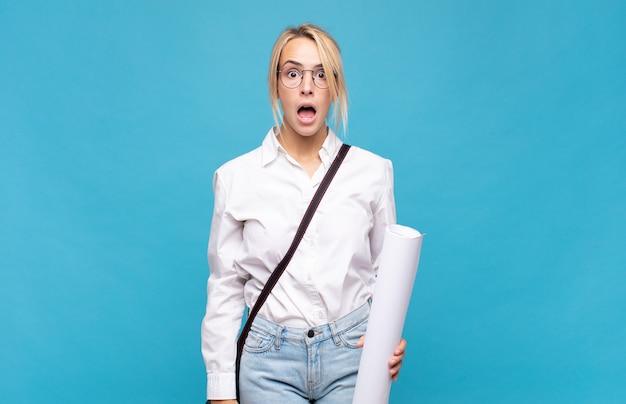 Молодая женщина-архитектор выглядит очень шокированной или удивленной, смотрит с открытым ртом и говорит:
