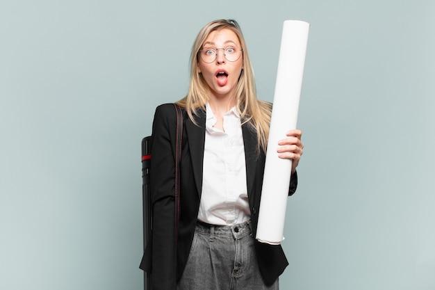非常にショックを受けた、または驚いたように見える若い建築家の女性は、すごいことを言って口を開けて見つめています