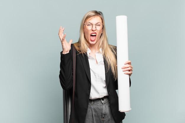 空中で手を上げて叫んで、激怒、欲求不満、ストレス、動揺を感じている若い建築家の女性