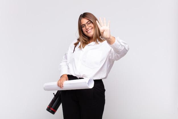 Молодая женщина-архитектор улыбается и выглядит дружелюбно, показывая номер четыре или четвертый с рукой вперед, отсчитывая