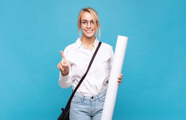 Молодая женщина-архитектор улыбается и выглядит дружелюбно, показывая номер один или сначала рукой вперед, отсчитывая