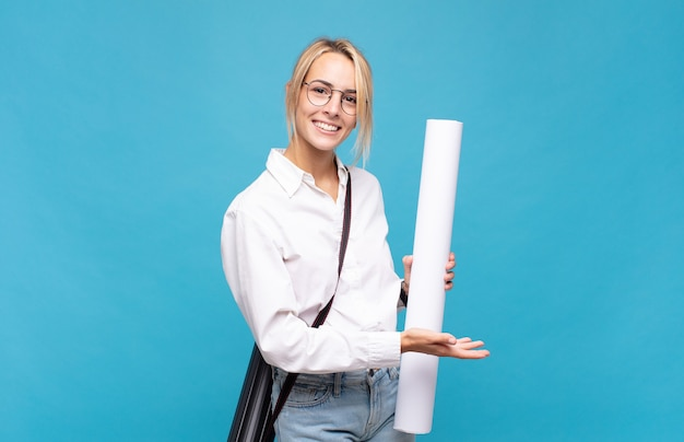 Молодая женщина-архитектор весело улыбается, чувствует себя счастливой и показывает концепцию в копировальном пространстве ладонью