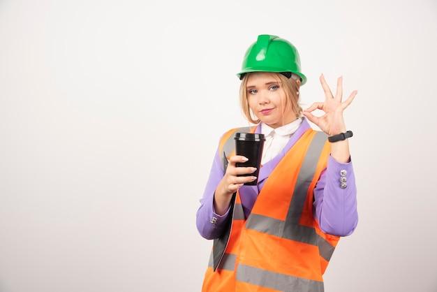 Молодая женщина архитектора с доской сзажимом для бумаги и черной чашкой показывая одобренный жест на белизне.