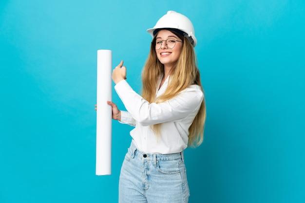 Молодая женщина-архитектор в шлеме и держит чертежи, изолированные на синей стене, указывая назад