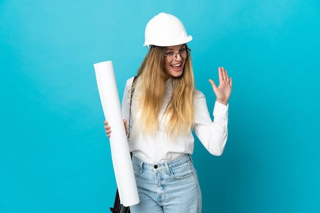 ヘルメットと幸せな表情で手で敬礼する青い壁に分離された青写真を保持している若い建築家の女性