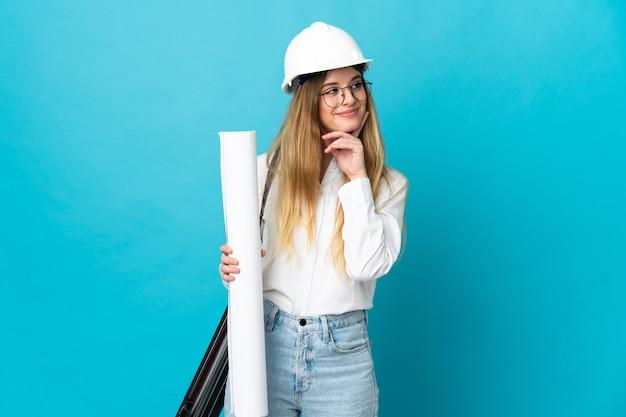 헬멧을 가진 젊은 건축가 여자를 찾는 동안 아이디어를 생각하는 파란색 벽에 고립 된 청사진을 들고