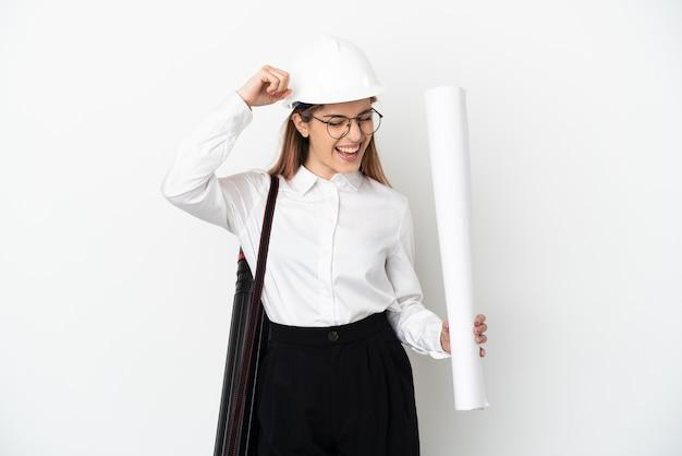 勝利を祝う白い背景で隔離のヘルメットと青写真を保持している若い建築家の女性