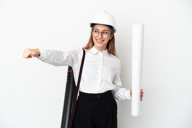 헬멧과 지주 청사진 젊은 건축가 여자 엄지 손가락 제스처를주는 흰색 배경에 고립