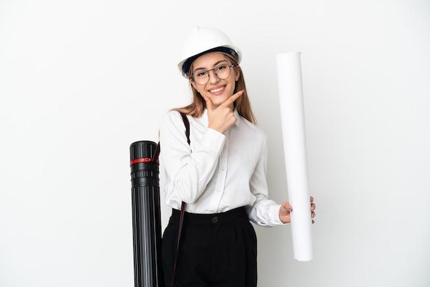 ヘルメットと白い背景で隔離の青写真を保持している幸せと笑顔の若い建築家の女性