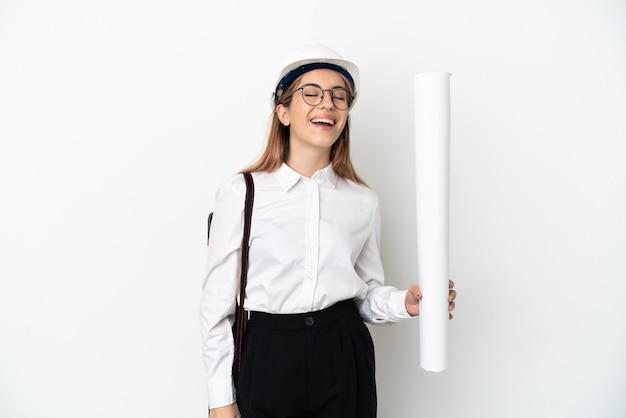 헬멧과 흰색 배경 웃음에 고립 된 청사진을 들고 젊은 건축가 여자