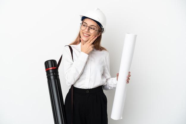 헬멧과 웃는 동안 찾고 흰색 배경에 고립 된 청사진을 들고 젊은 건축가 여자