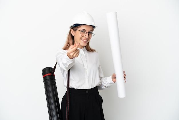 헬멧과 돈 제스처를 만드는 흰색 배경에 고립 된 청사진을 들고 젊은 건축가 여자