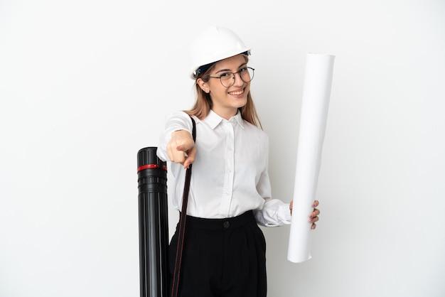 헬멧을 가진 젊은 건축가 여자와 행복 한 표정으로 앞을 가리키는 흰색 배경에 고립 된 청사진을 들고