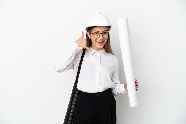Молодая женщина архитектора с шлемом и держа светокопий изолированные на белизне делая жест телефона. перезвони мне знак