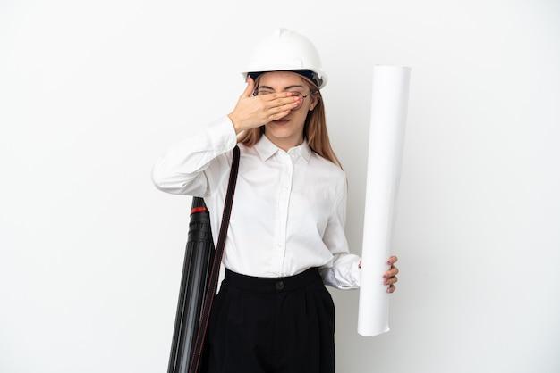 헬멧과 손으로 눈을 덮고 흰 벽에 고립 된 청사진을 들고 젊은 건축가 여자. 뭔가보고 싶지 않아