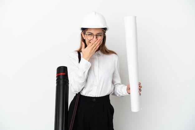 헬멧을 가진 젊은 건축가 여자와 흰 벽에 고립 된 청사진을 들고 행복하고 손으로 입을 덮고 웃고