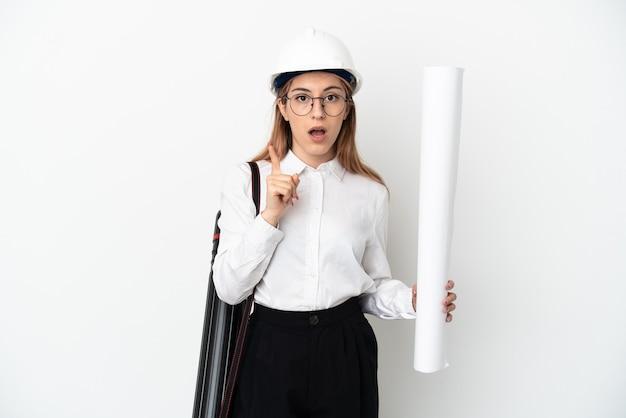 헬멧을 가진 젊은 건축가 여자와 손가락을 들어 올리는 동안 솔루션을 실현하려는 흰 벽에 고립 된 청사진을 들고