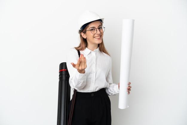 헬멧과 손으로와 서 초대하는 흰 벽에 고립 된 청사진을 들고 젊은 건축가 여자. 와줘서 행복해