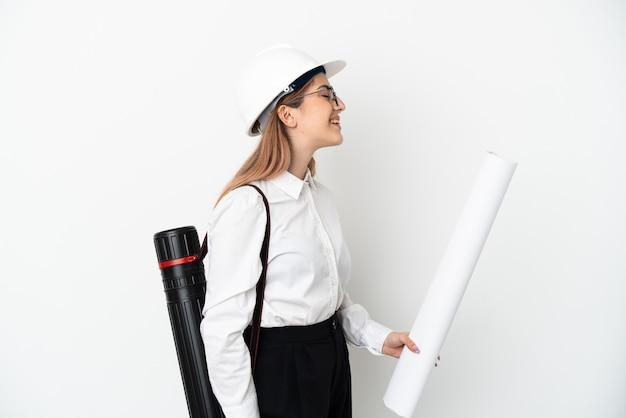 헬멧을 가진 젊은 건축가 여자와 측면 위치에서 웃고 흰 벽에 고립 된 청사진을 들고
