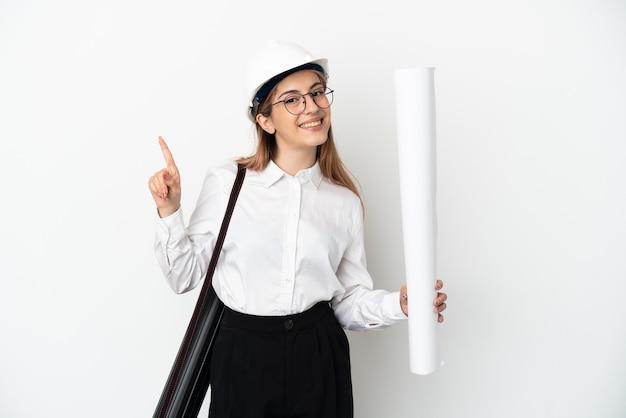 헬멧을 가진 젊은 건축가 여자와 흰 벽에 고립 된 청사진을 들고 최고의 기호에 손가락을 들어 올려