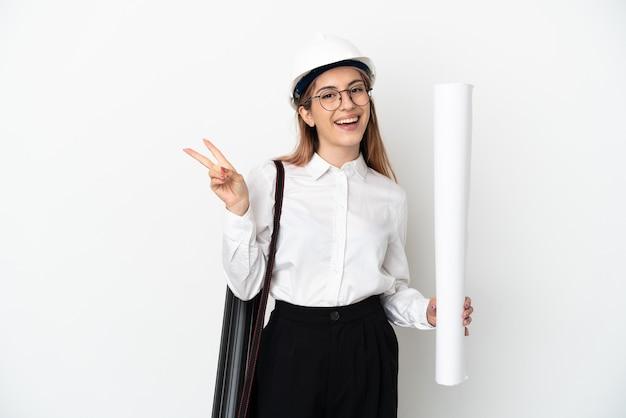 헬멧과 지주 청사진 웃 고 승리 기호를 보여주는 흰 벽에 고립 된 젊은 건축가 여자