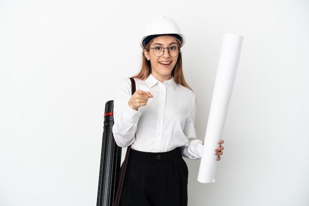 젊은 건축가 헬멧과 지주 청사진 놀라게 하 고 앞을 가리키는 흰 벽에 고립 된 여자