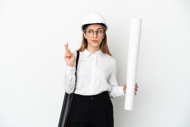 헬멧을 가진 젊은 건축가 여자와 손가락을 건너와 최고를 바라는 흰 벽에 고립 된 청사진을 들고