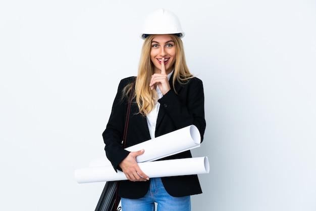 헬멧과 격리 된 흰색 침묵 제스처를 하 고 청사진을 들고 젊은 건축가 여자