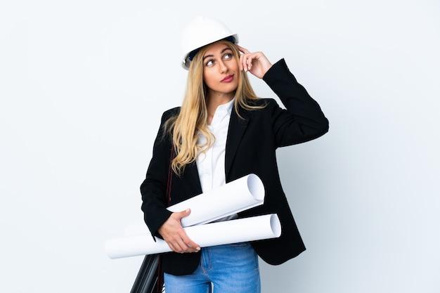 Молодая женщина архитектор с шлемом и проведение чертежи над изолированной белой стене, с сомнением и с смутным выражением лица
