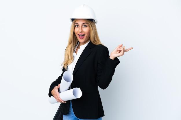 헬멧과 측면에 손가락을 가리키는 격리 된 흰 벽 위에 청사진을 들고 젊은 건축가 여자
