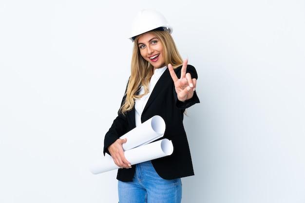 헬멧 및 격리 된 흰 벽 웃 고 승리 기호를 보여주는 청사진을 들고 젊은 건축가 여자