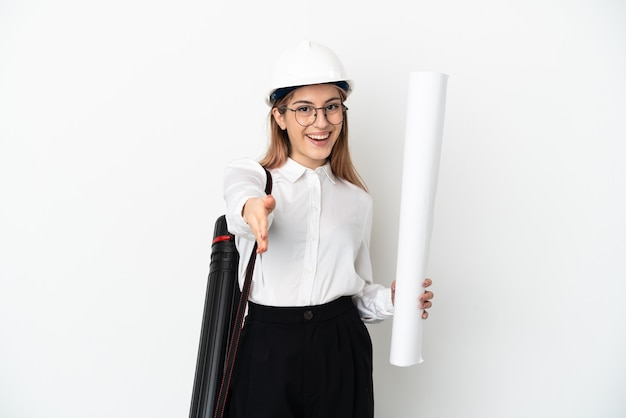 Young architect woman with helmet and holding blueprints isolated on white background shaking hands for closing a good deal