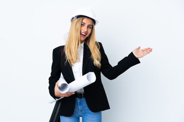 Young architect woman with helmet and holding blueprints over isolated white extending hands to the side for inviting to come