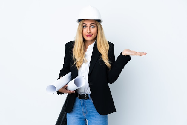 Young architect woman with helmet and holding blueprints over isolated white having doubts with confuse face expression