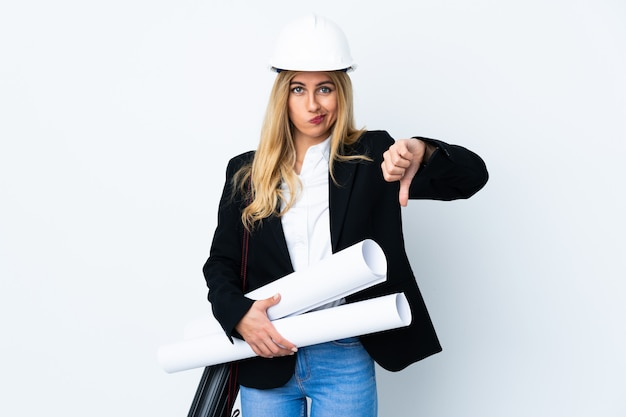 Young architect woman with helmet and holding blueprints over isolated white showing thumb down sign