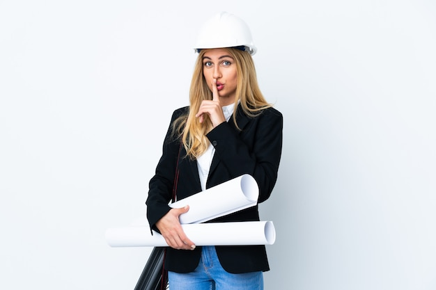 Young architect woman with helmet and holding blueprints over isolated white wall doing silence gesture