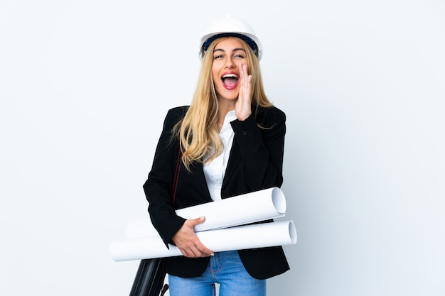 Young architect woman with helmet and holding blueprints over white wall shouting with mouth wide open