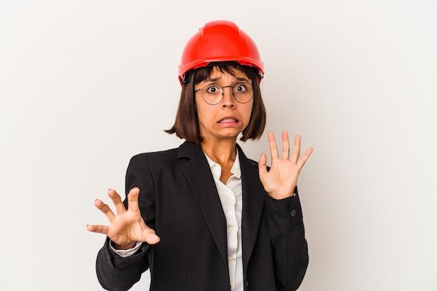差し迫った危険のためにショックを受けている白い背景で隔離の赤いヘルメットを持つ若い建築家の女性