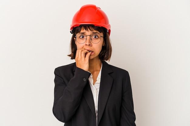 指の爪を噛んで、神経質で非常に心配している白い背景で隔離の赤いヘルメットを持つ若い建築家の女性。