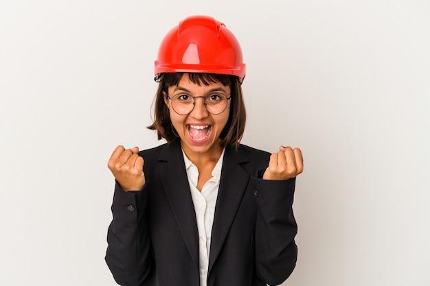のんびりと興奮して応援白い背景に分離された赤いヘルメットを持つ若い建築家の女性。勝利の概念。