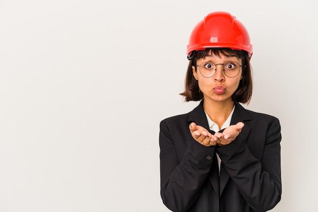 唇を折り畳み、空気のキスを送信するために手のひらを保持している白い背景で隔離の赤いヘルメットを持つ若い建築家の女性。