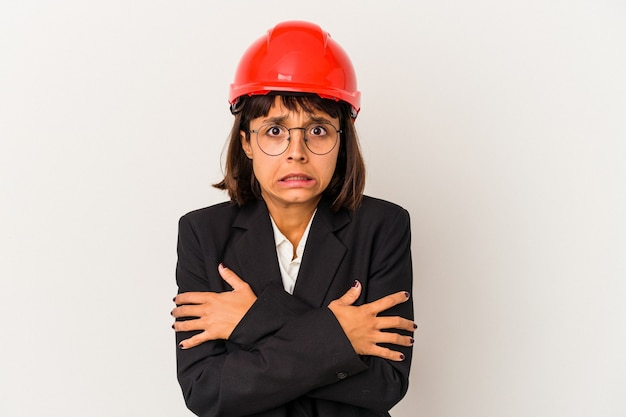 低温または病気のために寒くなる白い背景で隔離の赤いヘルメットを持つ若い建築家の女性。
