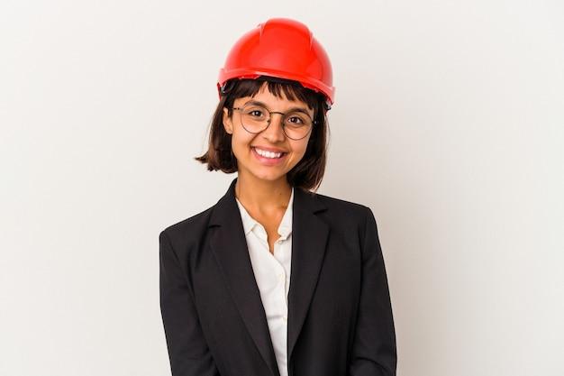 白い背景に分離された赤いヘルメットを持つ若い建築家の女性幸せ、笑顔、陽気な。