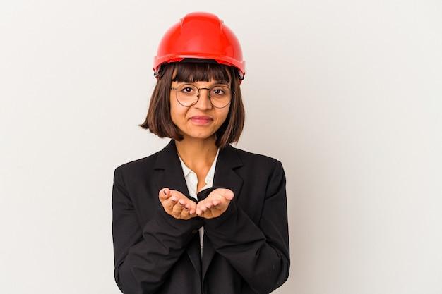 手のひらで何かを保持し、カメラに提供する白い背景で隔離の赤いヘルメットを持つ若い建築家の女性。