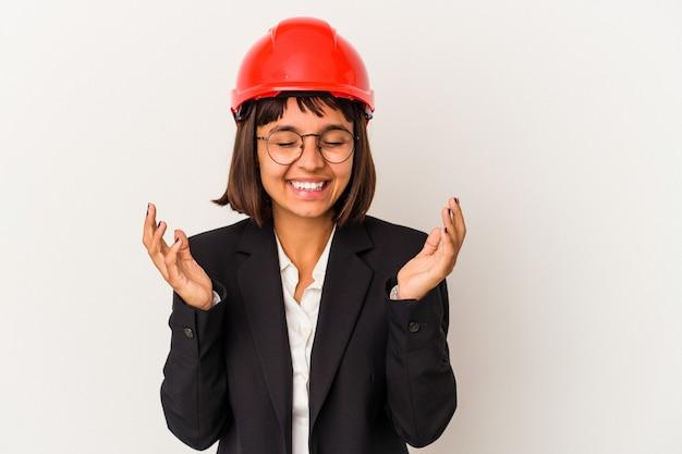 たくさん笑ってうれしそうな白い背景に分離された赤いヘルメットを持つ若い建築家の女性。幸福の概念。
